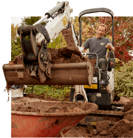 Man on digger completing landscaping Leamington Spa & landscaping Warwickshire.
